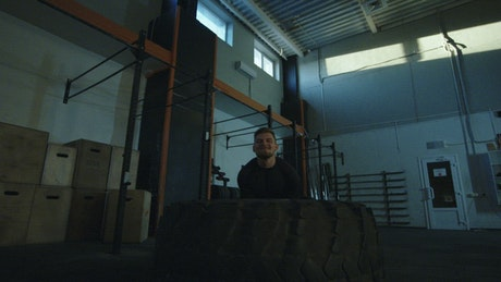 Man doing Crossfit exercises with a big tire