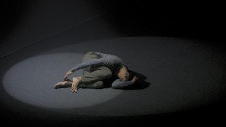 Man doing floor performance in the dark