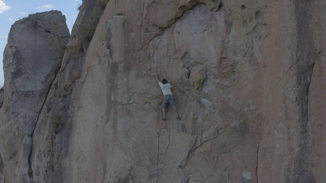 Man doing mountaineering on a large rocky mountain