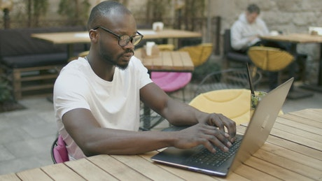 Man doing online research in outdoor cafe