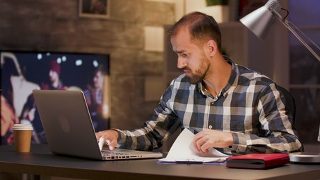Man doing research on laptop from home office