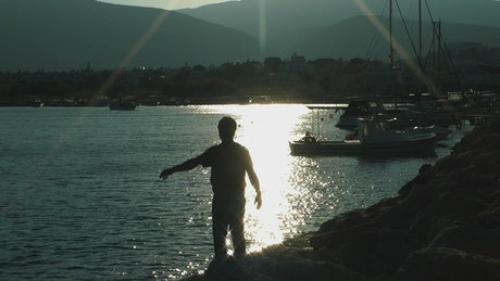 Man doing stretching in port at sunrise