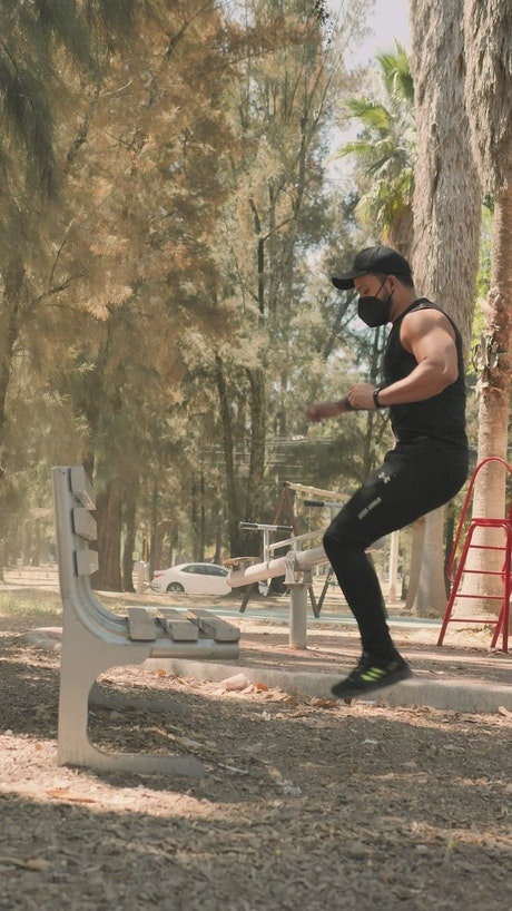 Man doing workout on a park bench