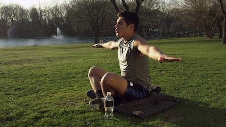 Man doing Yoga by a city lake