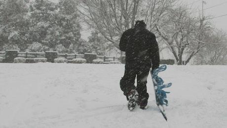 Man dragging his snowboard