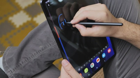 Man drawing on a tablet and with a touch pen