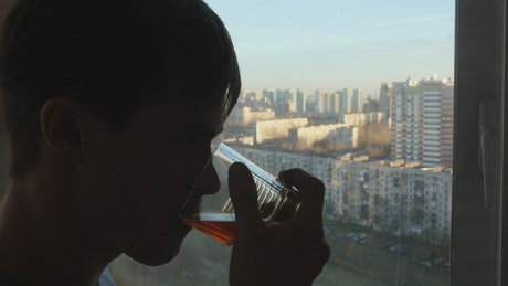 Man drinking alcohol by the window