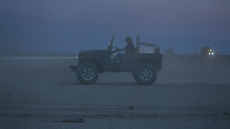 Man driving a Jeep in the desert at night