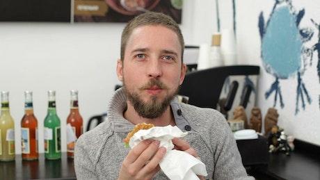 Man eating a burger and smiling