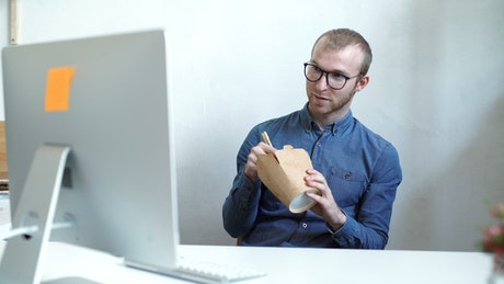 Man eats chinese food on work break in office