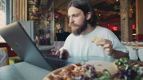 Man eats pizza while woking on laptop at hip cafe