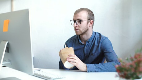 Man eats take-out food at desk in minimal office