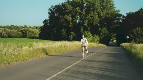 Man enjoys bicycle ride in sunny countryside