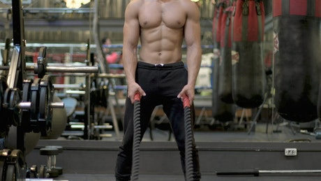 Man exercising hard with a pair of ropes