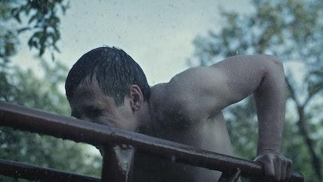 Man exercising outdoors while raining