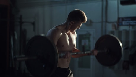 Man exercising with the barbell at the gym