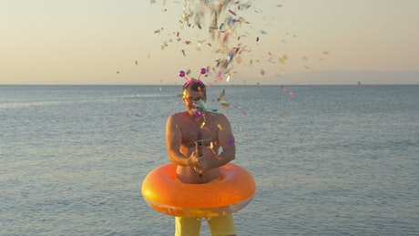 Man firing confetti at the beach