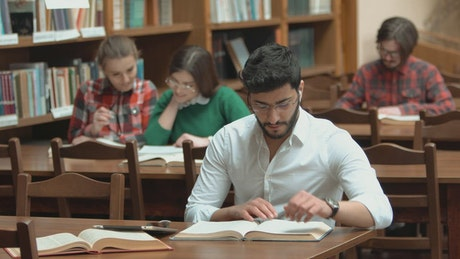 Man focused on study for exam in library