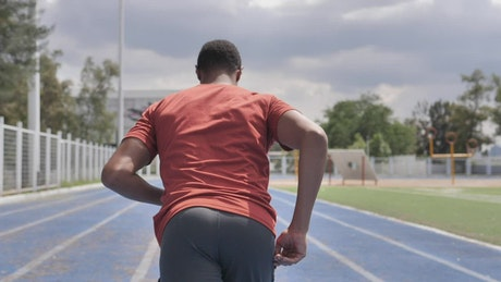 Man from behind running in a sports center