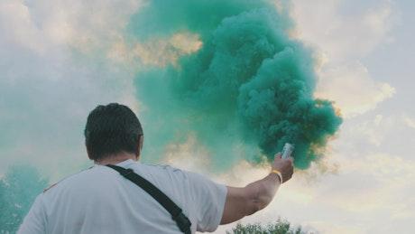 Man from behind waving a smoke bomb