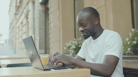 Man gets emotional while chatting online outside ith laptop