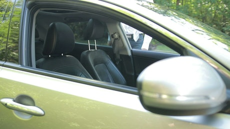 Man getting into a car and putting on a seat belt