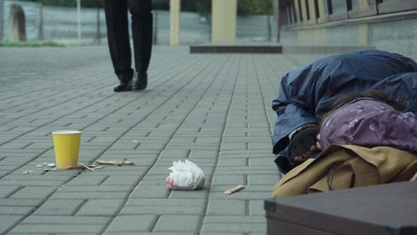 Man giving coins to homeless person