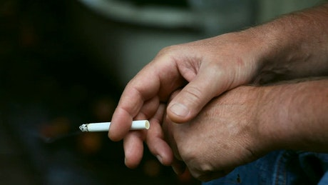 Man hand holding a lit cigarette