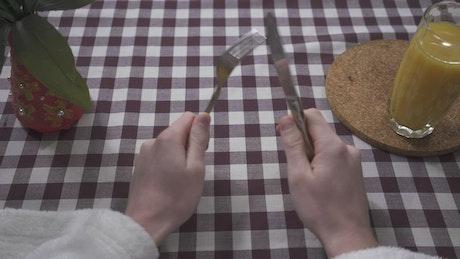 Man hands rub together fork and knife
