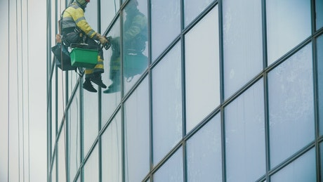 Man hanging on ropes cleaning windows in a building