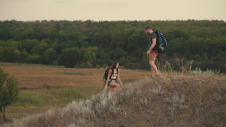 Man helps his friend to climb a mound in nature