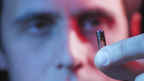 Man holding a small microchip
