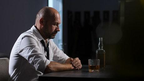 Man holding his head at a bar