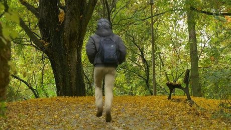 Man hurries to bench in a park at autumn