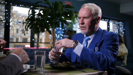 Man in a blue suit talking over dinner