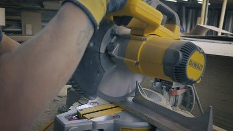 Man in a carpentry cutting with an electric saw