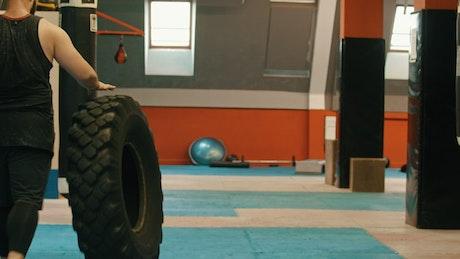 Man in a gym walking with a big truck wheel