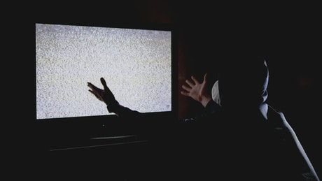 Man in a hoodie in front of a TV with static