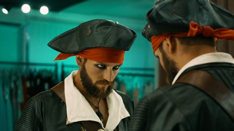 Man in a pirate costume grimacing to the mirror