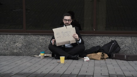 Man in a suit begging on the street