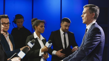 Man in a suit gives an interview to reporters