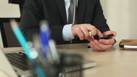Man in a suit in his office using his cellphone