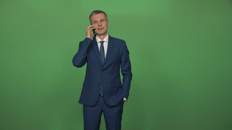 Man in a suit on a phone call in front of a green screen