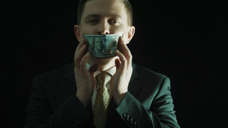 Man in a suit putting money on his mouth