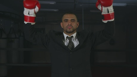 Man in a suit wearing red boxing gloves
