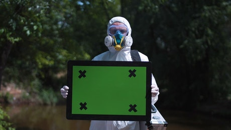 Man in biohazard suit holding a greenscreen sign