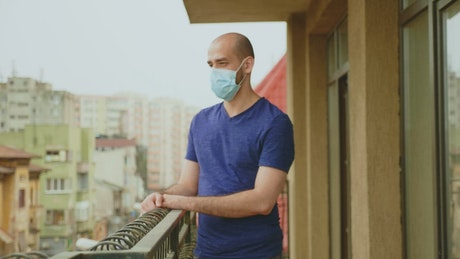 Man in Coronavirus lockdown hangs head on balcony