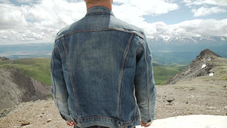 Man in denim jacket raises arms to mountain landscape