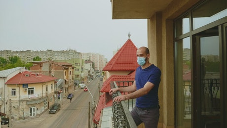 Man in face mask thinks about quarantine on balcony