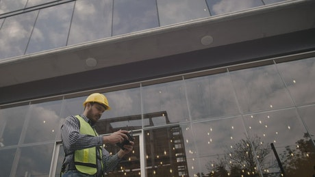 Man in hard hat flying a drone